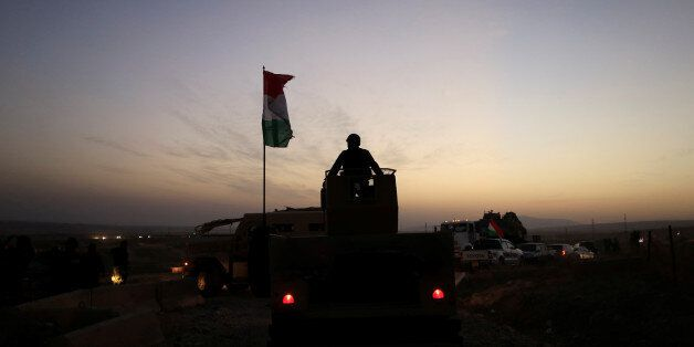 A Kurdish Peshmerga fighter looks over as he stands on the top of a humvee in front of an Islamic State...