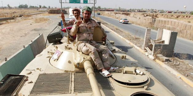 Members of Iraqi security forces gesture as a convoy advances on the outskirts of Mosul, to fight against...