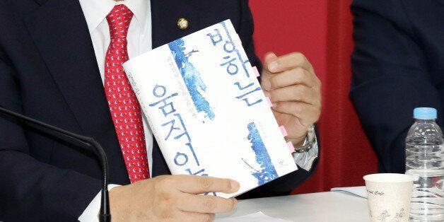 새누리당 정진석 원내대표가 17일 오전 국회에서 열린 최고위원회의에서 '송민순 회고록'인 '빙하는 움직인다-비핵화와 통일외교의 현장'을 들어 보이고