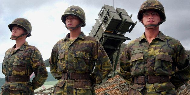 ** FILE *Taiwanese soldiers stand at attention in front of one of Taiwan's many Patriot missile air defense...