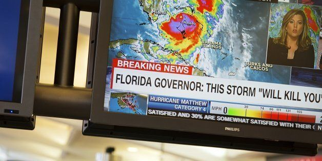 A monitor shows a television news report on Hurricane Matthew as travelers collect their baggage after...