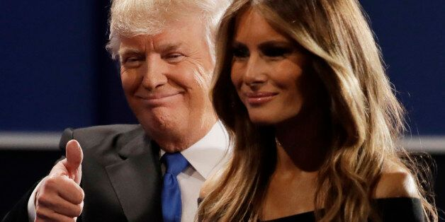 Republican presidential nominee Donald Trump walks off the stage with his wife Melania Trump, wife of...