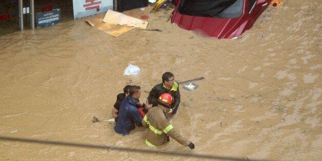 태풍 차바의 영향으로 울산에 300㎜가 넘는 폭우가 쏟아지면서 곳곳이 침수됐다. 목까지 물에 잠기는 중구 우정동에서 소방관들이 고립된 시민을 구조하고