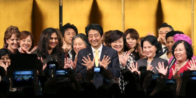 Japanese Prime Minister Shinzo Abe, center, poses for a photo with participants during a reception of...