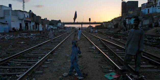 A Pakistani boy plays with a kite between railway tracks in Karachi, Pakistan, Tuesday, Oct. 29, 2013....