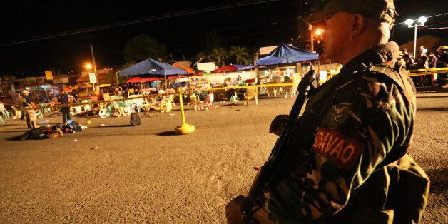 A Philippine soldier keeps watch at a blast site at a night market that has left several people dead...