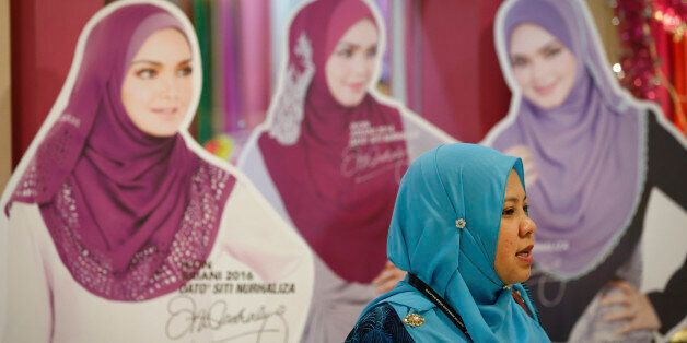 A Muslim woman walks by cutouts displayed during the World Muslim Women Summit and Exhibition in Kuala...