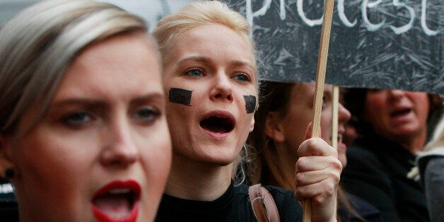 Polish women shout slogans during a nationwide strike and demonstration to protest a legislative proposal...