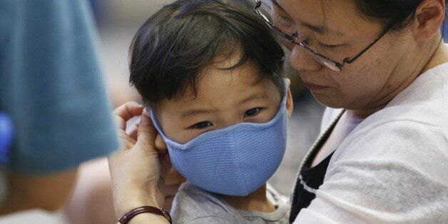 A passenger puts a masks on her son to prevent contracting Middle East Respiratory Syndrome (MERS) at...