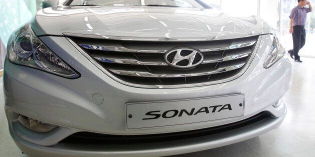 An employee walks past Hyundai Motor's Sonata, on display at the automaker's dealership in Seoul September...