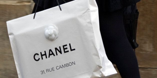 A woman walks with a shopping bag from fashion house Chanel in central Paris October 13, 2008. REUTERS/Charles...