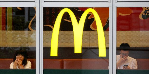 Customers using mobile phones, are seen through the windows of a McDonald's store in Tokyo, Japan July...