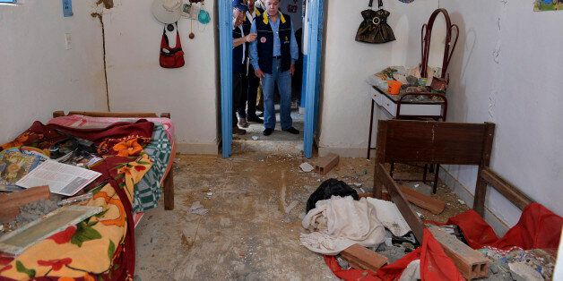 Colombia's President Juan Manuel Santos (C) inspects a house partially damaged by an earthquake in Betulia,...