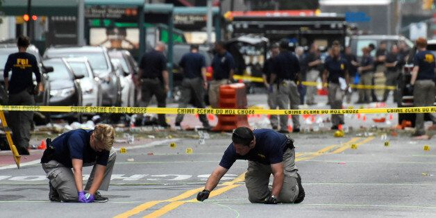 Federal Bureau of Investigation (FBI) officials mark the ground near the site of an explosion in the...