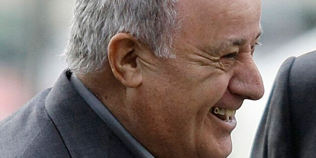Amancio Ortega, chairman of Spanish global fashion group Inditex, laughs during a visit of Spain's Princess...