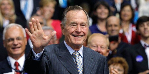Former U.S. President George H.W. Bush reacts to the cheers of the crowd as he arrives at the second...