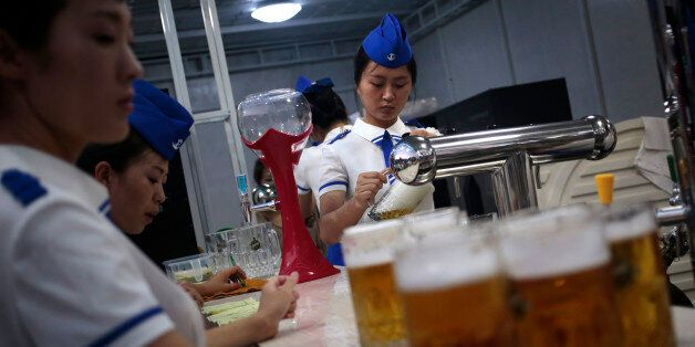 A waitress fill up jugs of beer during Taedonggang Beer Festival in Pyongyang, North Korea, Sunday, Aug....