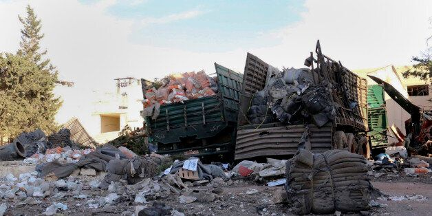This image provided by the Syrian anti-government group Aleppo 24 news, shows damaged trucks carrying...