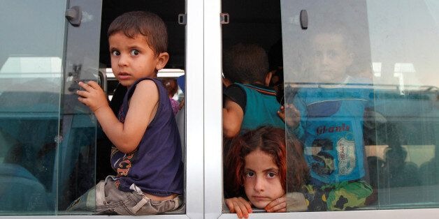 Displaced Iraqi children, who had fled to Syria to escape the violence in Mosul, transfer to a refugee...