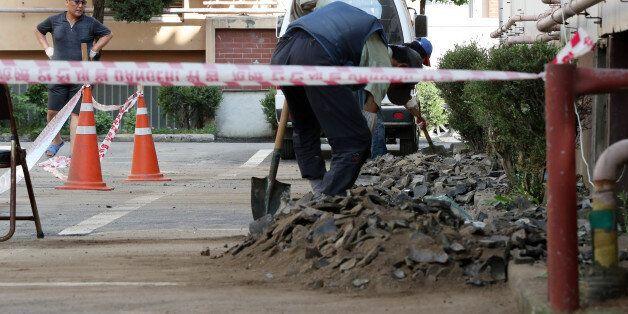 13일 오후 경북 경주시 성건동의 한 아파트에서 관계자들이 전날 발생한 지진의 영향으로 주차장에 떨어진 기와를 치우고