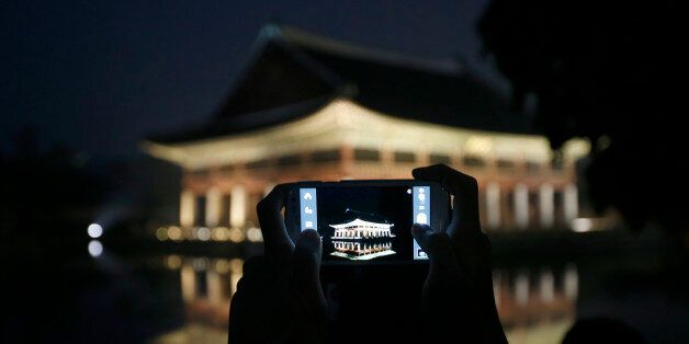 A visitor takes a photograph of Gyeonghoeru pavilion, a part of Gyeongbok palace, during the evening...