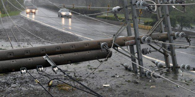 Cars drive past collapsed power lines, that partially block the road, as super typhoon Meranti skirts...