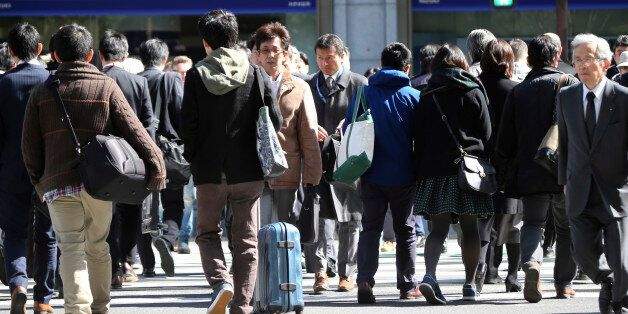 People cross a street in Tokyo, Friday, Feb. 26, 2016. The results of the 2015 census released Friday...