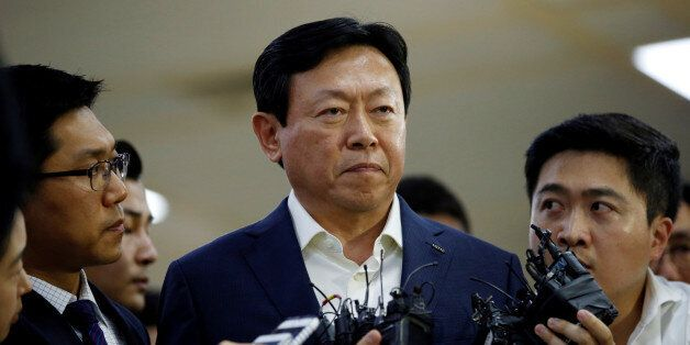Lotte Group Chairman Shin Dong-bin is surrounded by reporters as he makes his way upon his arrival at...