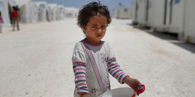 FILE - In this June 19, 2015 file photo, a Syrian refugee child walks at a refugee camp in Suruc, on...