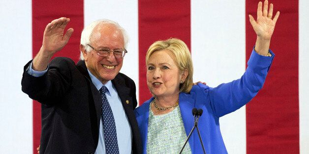 Democratic presidential candidate Hillary Clinton waves to supporters with Sen. Bernie Sanders, I-Vt.,...