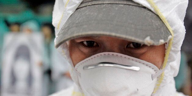 In this photo taken on March 25, 2010, a South Korean activist, wearing protective clothing, participates...