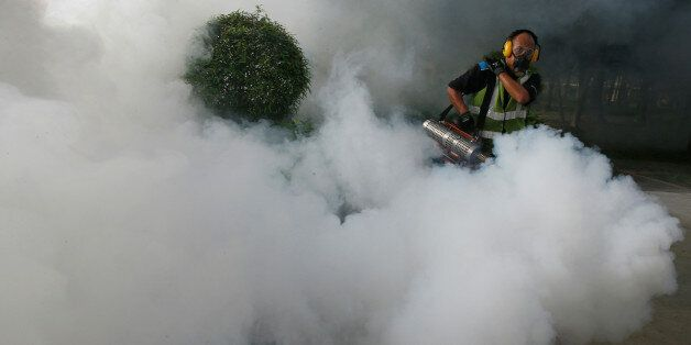 A worker fogs the common areas of a public housing estate at an area where locally transmitted Zika cases...