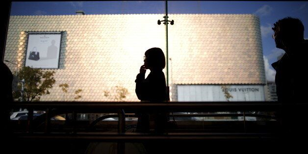 A woman is silhouetted against a department store at Apgujeong luxury shopping district in Seoul, South...