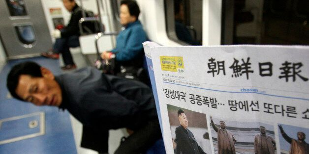 A subway passenger reads a South Korean newspaper Chosun Ilbo reporting North Korea's rocket launch in...