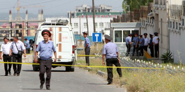 Investigators, Interior Ministry officers and members of security forces work near the site of a bomb...
