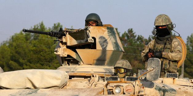 Turkish soldiers on an armoured personnel carrier drive towards the border in Karkamis on the Turkish-Syrian...