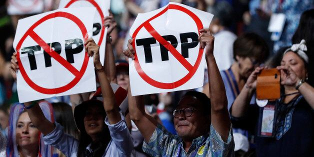 Delegates protesting against the Trans Pacific Partnership (TPP) trade agreement hold up signs during...