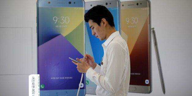 An employee uses a Samsung Electronics' Galaxy Note 7 new smartphone at its store in Seoul, South Korea,...