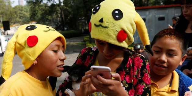 Children wearing hats of a Pokemon character, Pikachu, play Pokemon Go during a gathering to