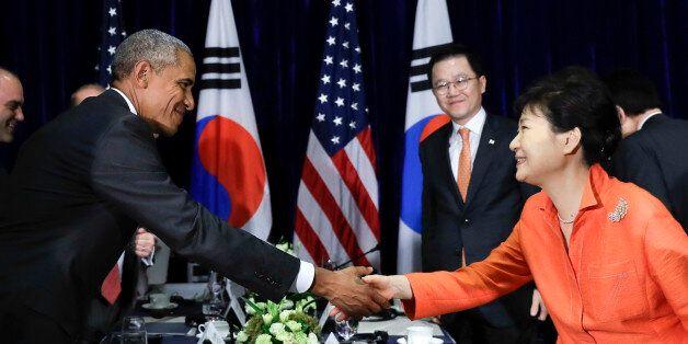 U.S. President Barack Obama, left, and South Korean President Park Geun-hye shake hands after speaking...