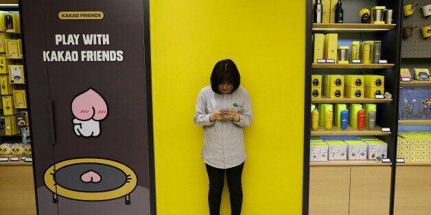 In the April 4, 2016, photo, Kim Do-hee, an employee of Kakao Friends Shop, uses a smartphone beside...