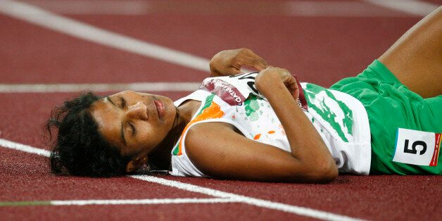India's Jaisha Orchatteri Puthiya Veetil lies on the track after the women's 5000m final at the 15th...