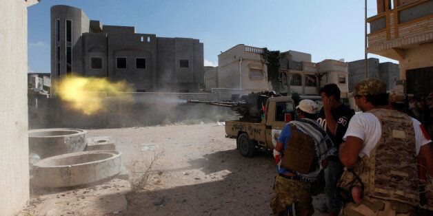 Members of Libyan forces allied with the UN-backed government fire a weapon towards Islamic State militants...