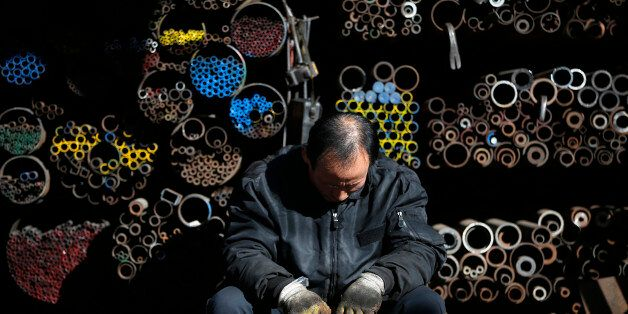 A worker takes a nap in front of steel products stacked at a steelworks in Seoul January 28, 2014. South...
