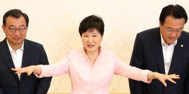 박근혜 대통령이 11일 낮 청와대에서 열린 새누리당의 새 지도부 초청 오찬에 앞서 기념촬영을 한 뒤 자리를 안내하는 손짓을 하고