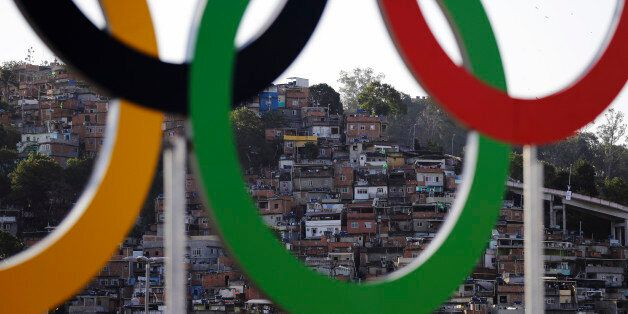 Houses from a favela are photographed through the Olympic rings prior to the opening ceremony for the...