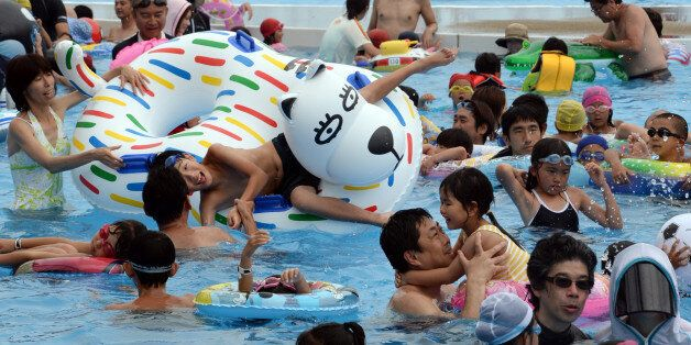 Visitors beat the summer heat at the Yomiuri Land Water Amusement Island (WAI) in Tokyo on July 14, 2013....
