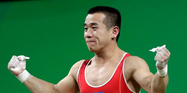 Om Yun Chol, of North Korea, celebrates a successful lift in the men's 56kg weightlifting competition...
