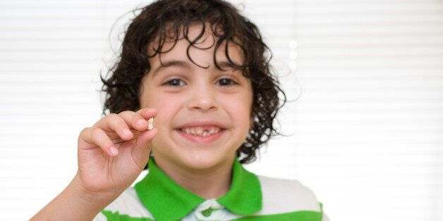 TORONTO, ONTARIO, CANADA - 2011/06/29: Human development stage: Child holding a baby tooth that has just...