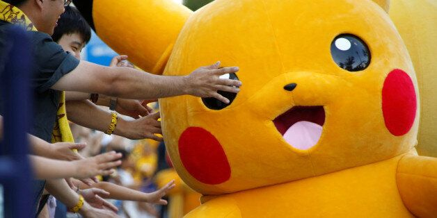 People touch a performer wearing Pokemon's character Pikachu costume during a parade in Yokohama, Japan,...